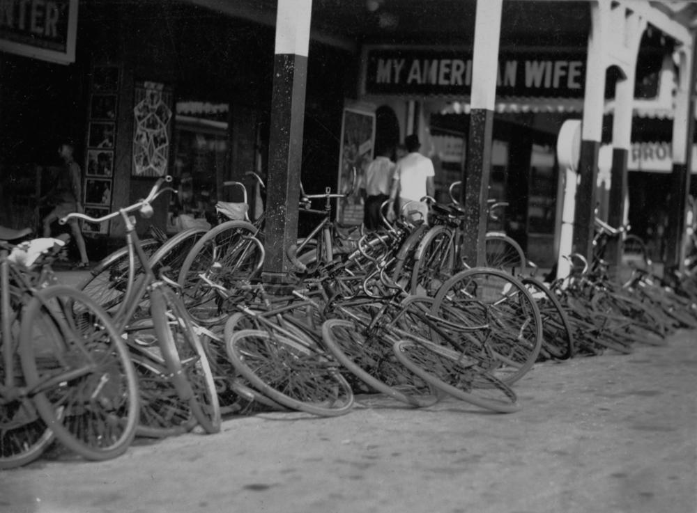 Black and white image showing numerous bikes that have been left on the street outside a cinema. Two people walk on the footpath outside the cinema, under a sign above which reads 'MY AMERICAN WIFE'