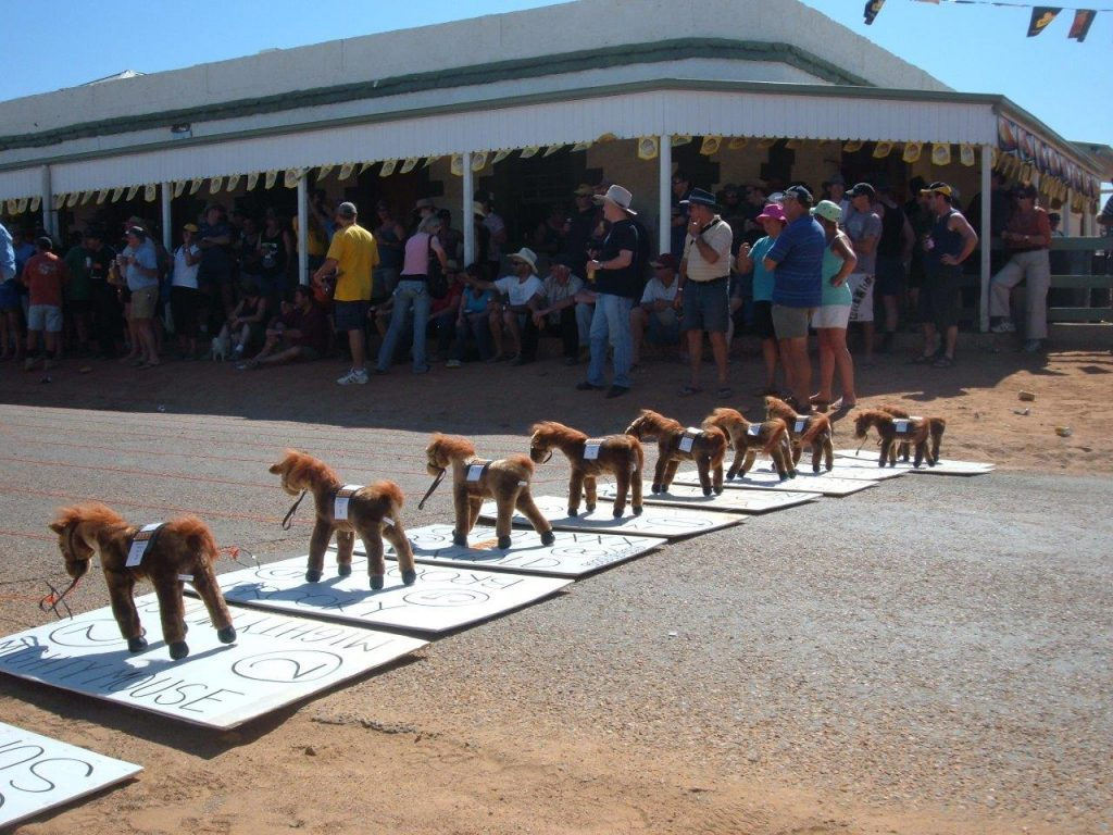 Colour photograph showing a row of nine small, toy horses on cardboard bases, lined up outside a hotel. A crowd of people has gathered in the background.
