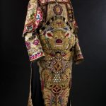 A long-sleeved embroidered cream silk jacket. The sleeves are in polished cotton with appliqued floral emblems and gold thread and silk embroidery.There are decorative panels attached over the shoulders and ties at waist level to attach the front and back sections. Below this the front and back panels are not attached to each other. In the upper front section there is a dragon face with a raised purple nose and red ears trimed with white fur. The lower front and back panels are lined with red cloth while the upper section is lined with cream cloth. The lower front panel has a double decorative layer.