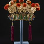 An elaborate Chinese headdress made up of a lower section painted in gold, red, green and blue. Above this there is a row of gold floral emblems to which are attached red pompoms.